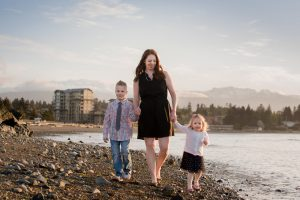 Mother and two children walking on a beach in Parksville