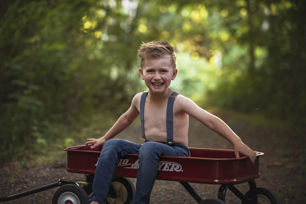 Image of young boy sitting in wagon in forest