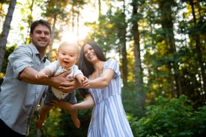 Family forest photography session with baby, mother and father. Family of three. woods trails golden hour