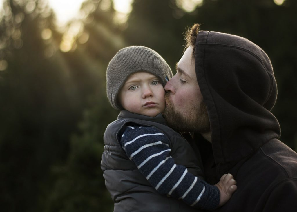 Photo of father kissing son's cheek in Qualicum Beach