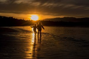 children running on the beach at sunset in Qualicum Beach