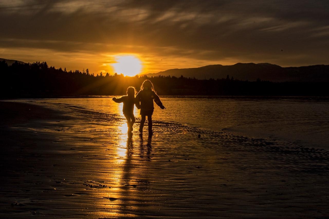 children running on the beach at sunset in Qualicum Beach