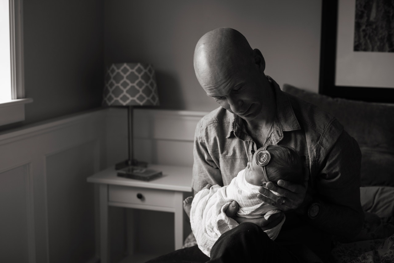 Lifestyle newborn image with newborn daughter in fathers arms