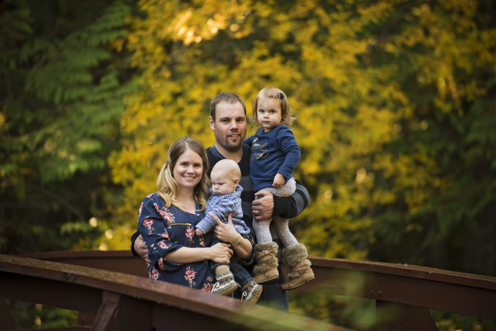 Family of four on Qualicum Falls bridge with fall leaves