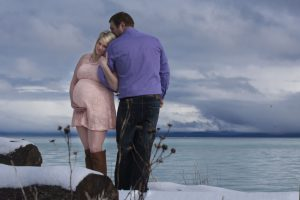 Maternity photo on snow covered beach with mother and father