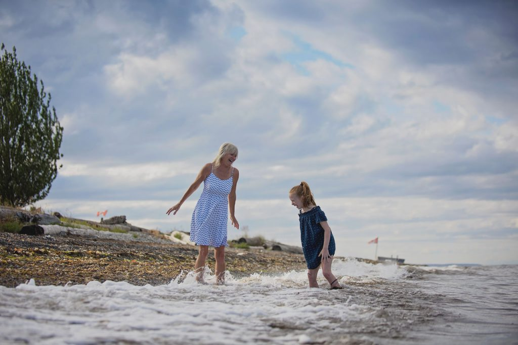 Woman and child playing in waves on beach