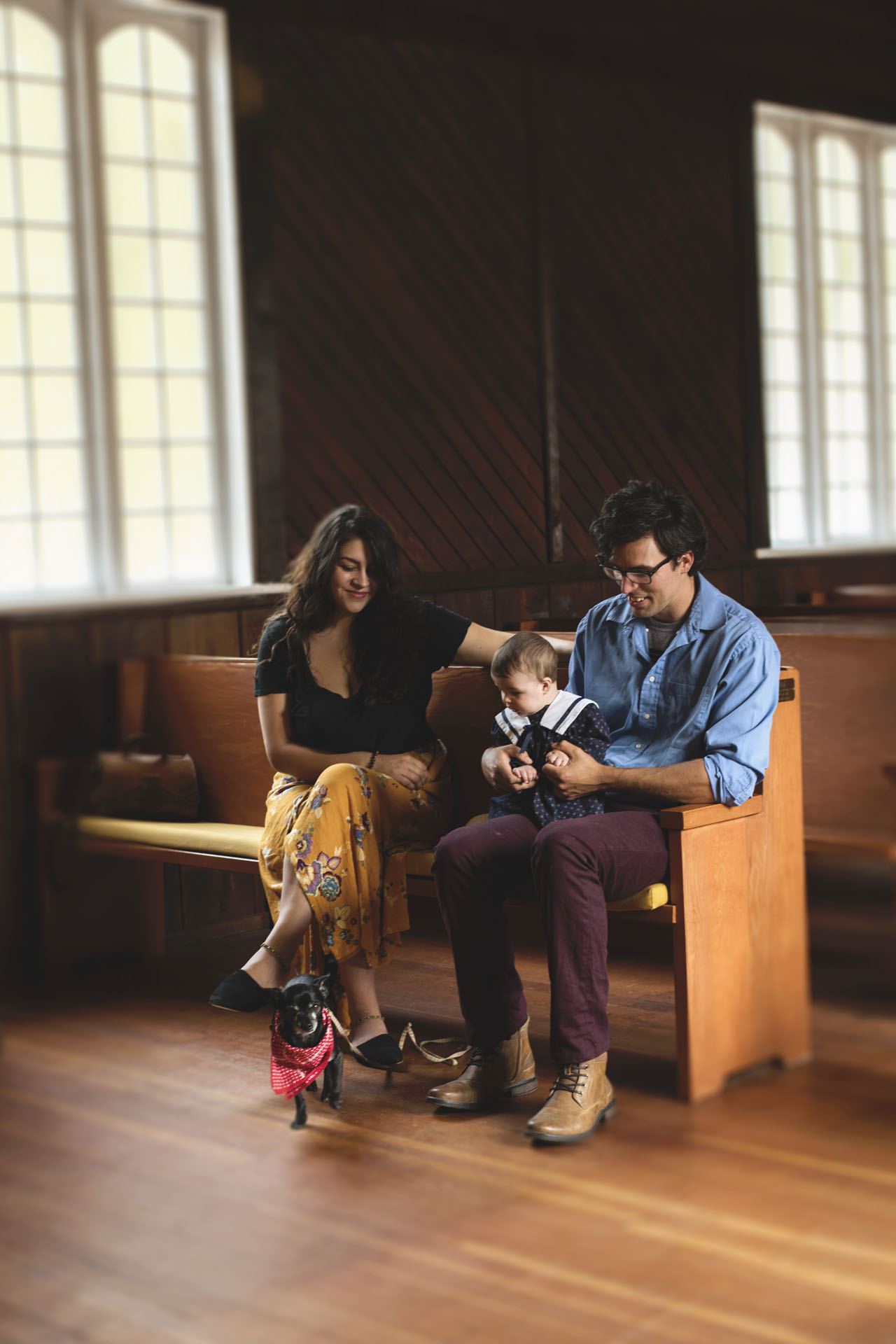 Mother, Father, young child, and dog on church pew