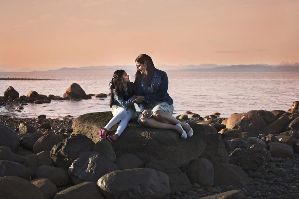 Mother and Daughter sitting on rocks on beach at dusk