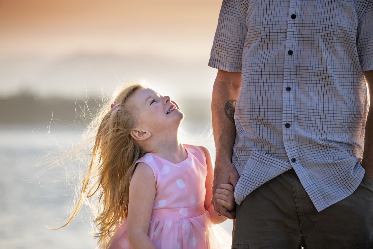 Family photography of daughter looking up at father on beach