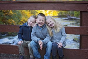Qualicum Falls family photo of 2 young brothers and sister sitting on bridge