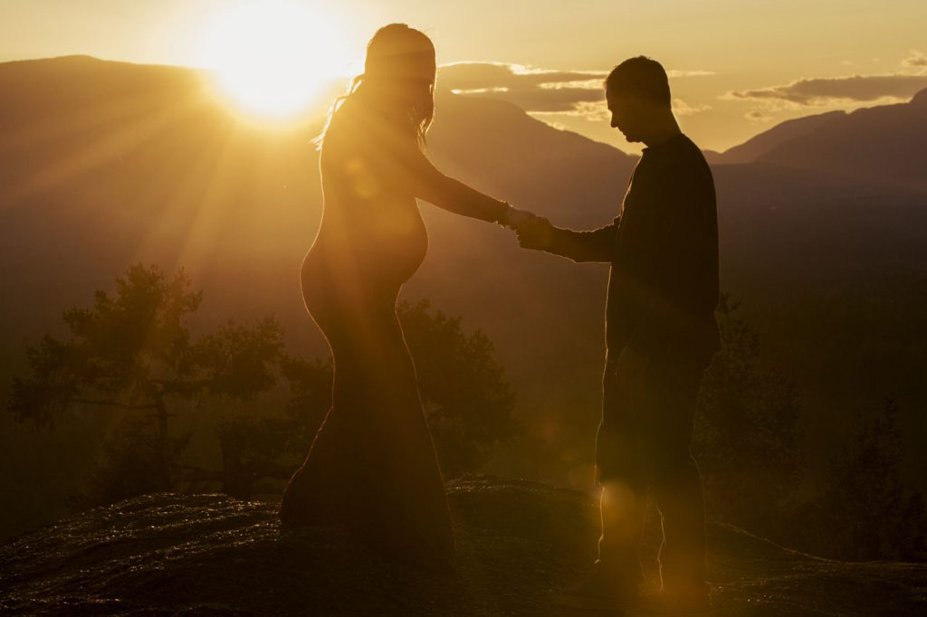 Maternity photography of couple's silhouette with sun setting in background  taken by photographer Alexandra Medd