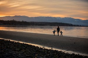 Family walking on beach in sunset session