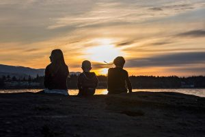 Sunset with three children sitting on a rock
