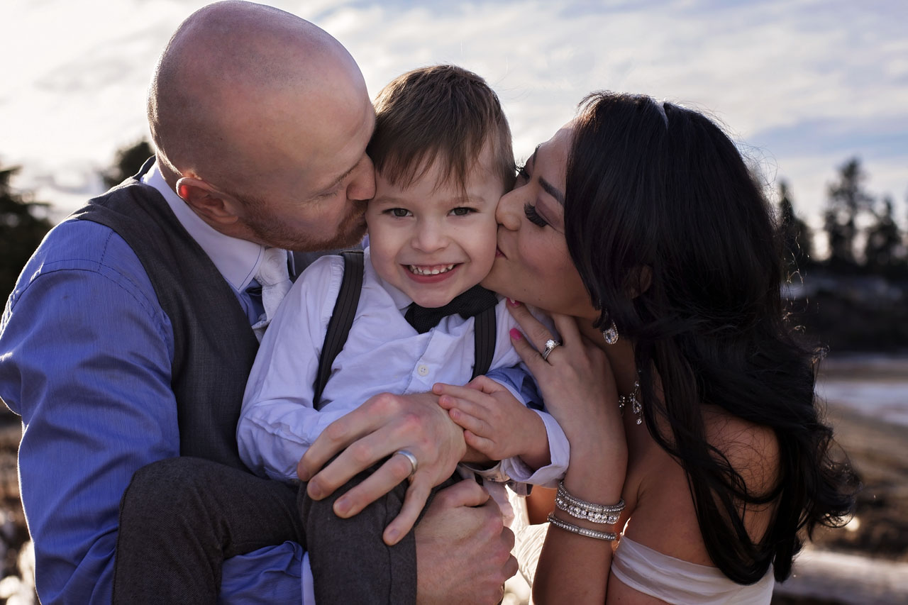 Parksville wedding photography of bride and groom kissing child's cheeks