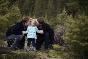 Family photo of mom and dad kissing daughter's cheek in forest