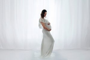 studio maternity session. Pregnant mother backlit on white in studio maternity gown