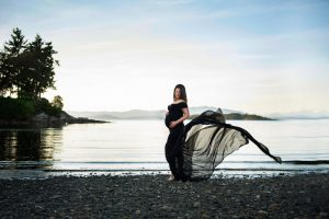 outdoor ocean beach maternity session in black flowing gown from maternity closet for clients to use