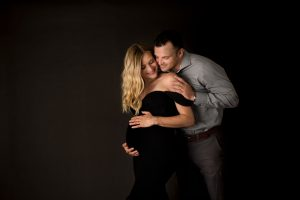 family maternity image in a gown with husband and wife on black seamless backdrop