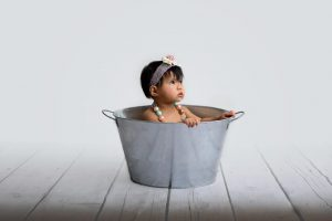 First birthday photo shoot of girl sitting in wash bucket