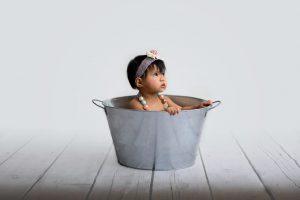 First birthday photo shoot of girl sitting in wash bucket