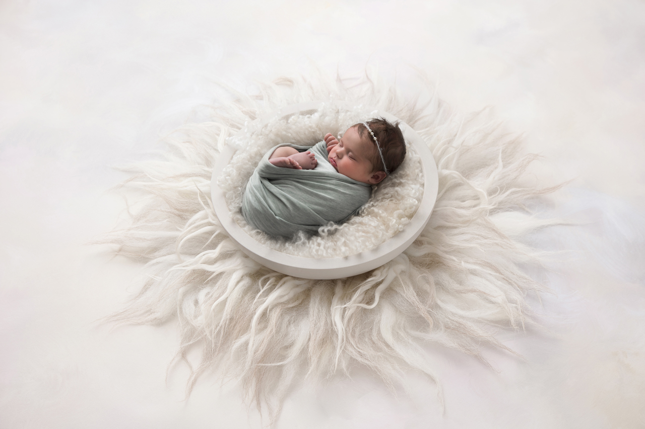 Simple swaddled newborn baby girl in green wrap backlit in white bowl on white backdrop