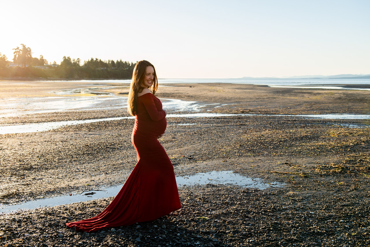 Pregnant woman in red dress on beach just before sunset walking towards horizon.